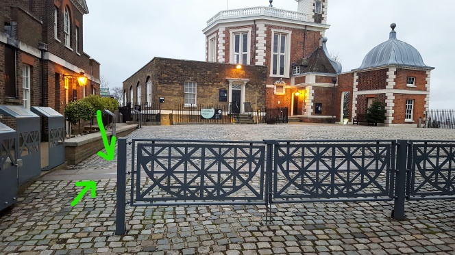 Cement prime meridian line seen from behind fencing.